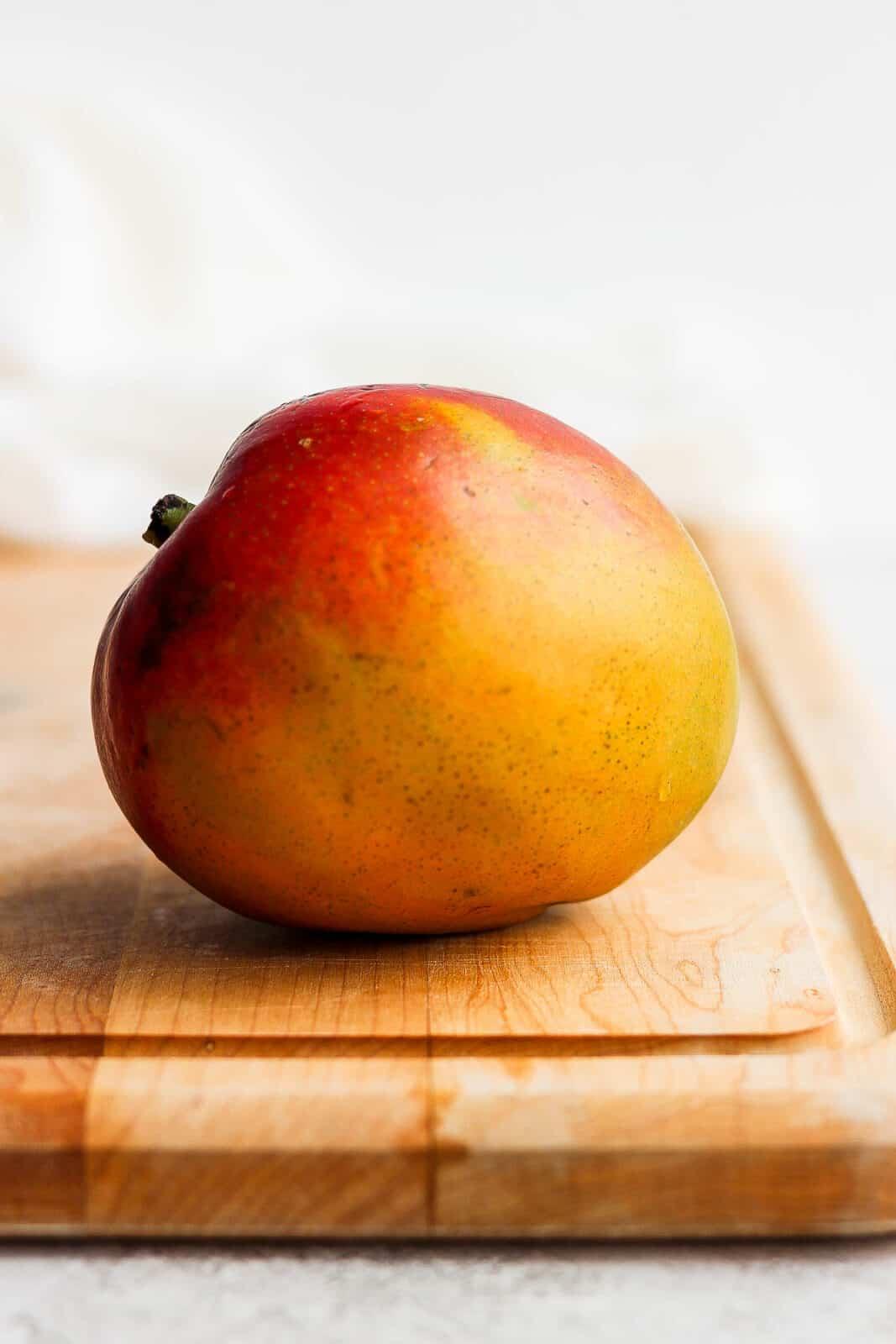 A ripe mango on a cutting board.