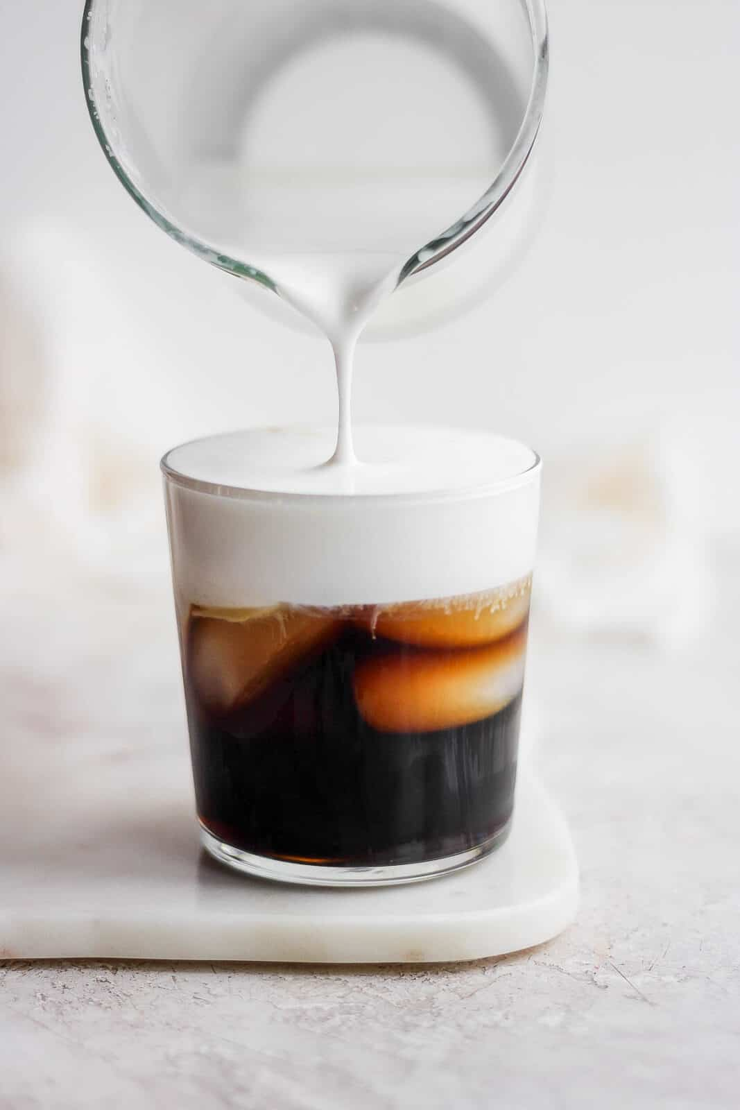 Someone pouring cold foam into a glass of cold brew coffee.