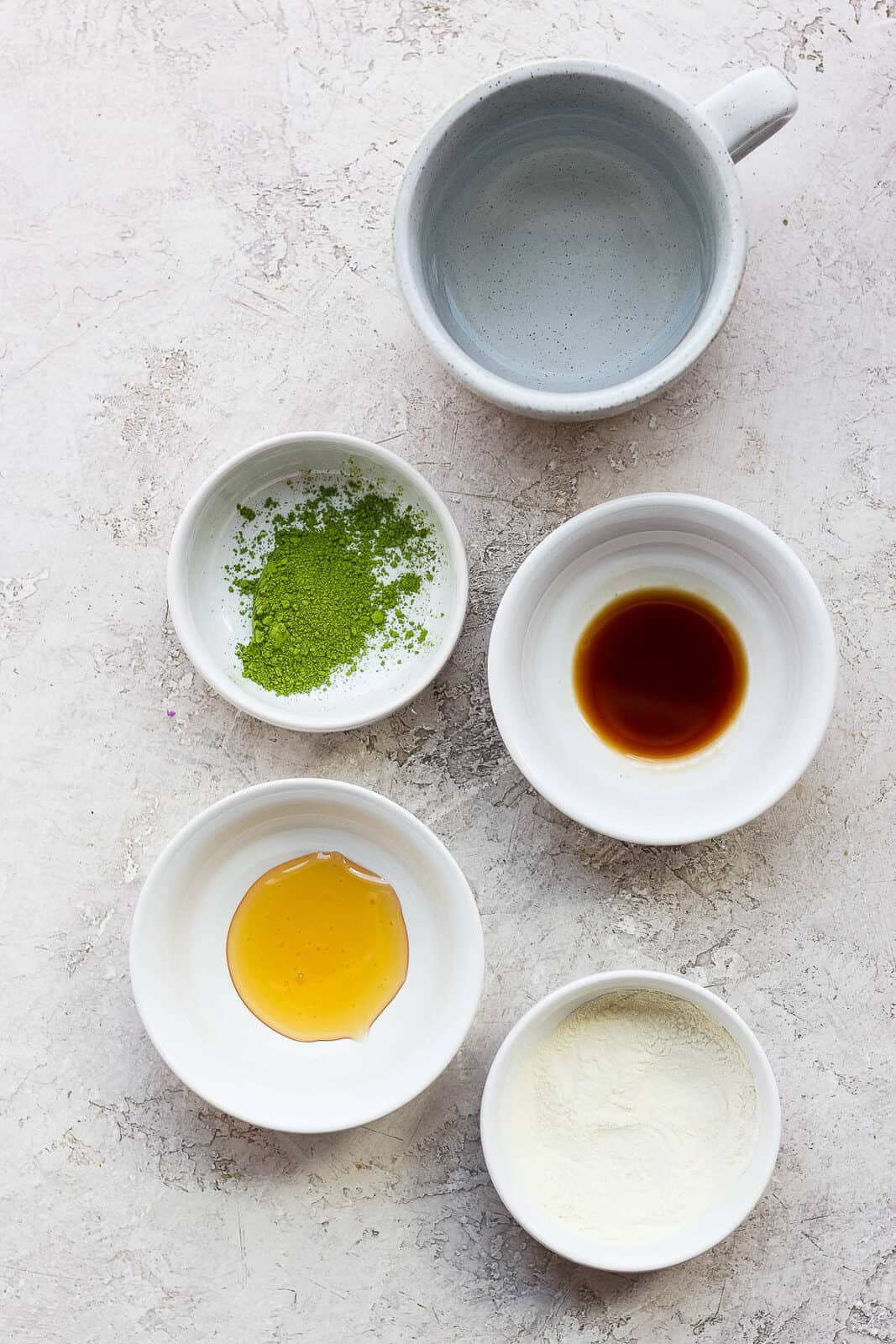 Ingredients for a matcha latte in small bowls.