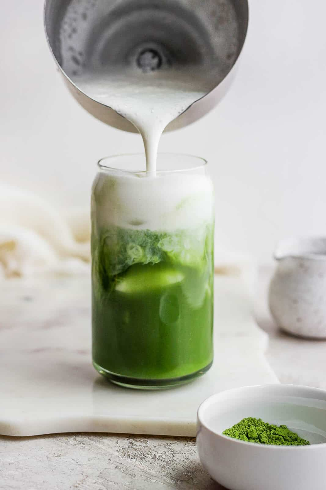 Someone pouring cold foam into a glass of iced matcha latte.