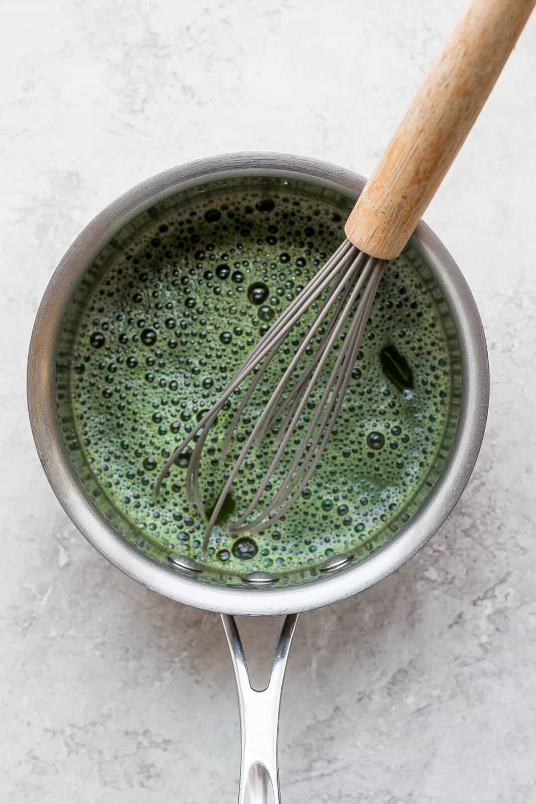 A small saucepan with matcha inside and a wooden whisk sticking out.