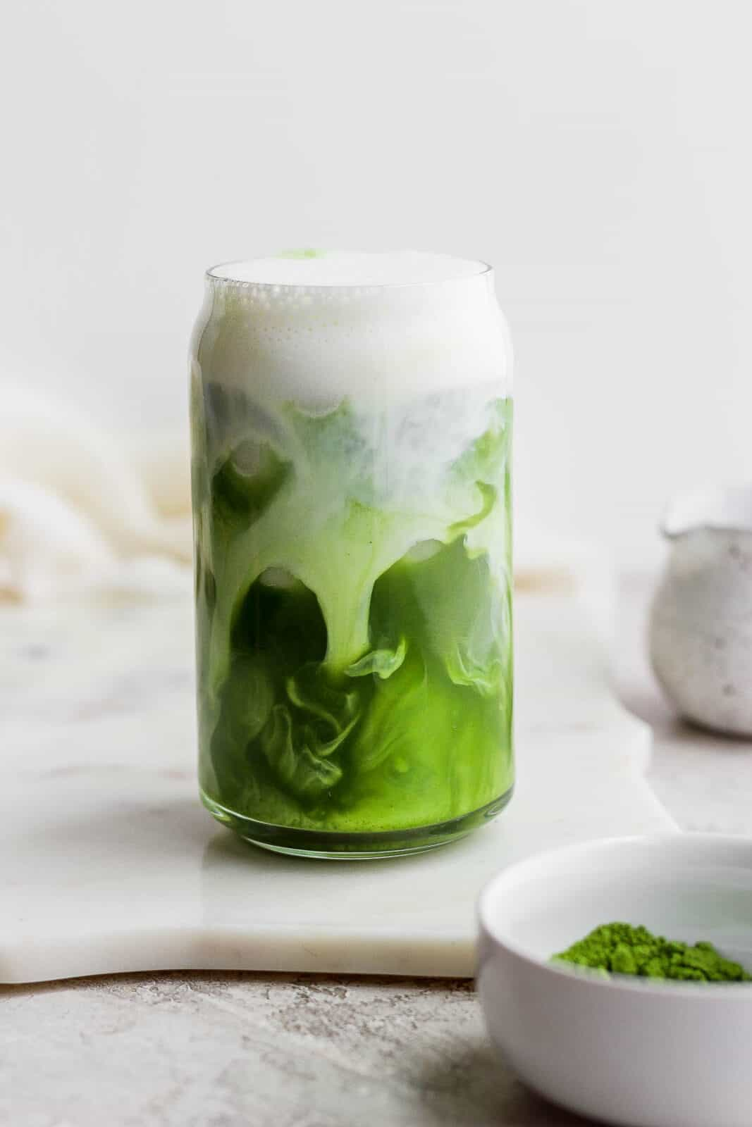A glass of iced matcha latte with almond milk swirling inside.