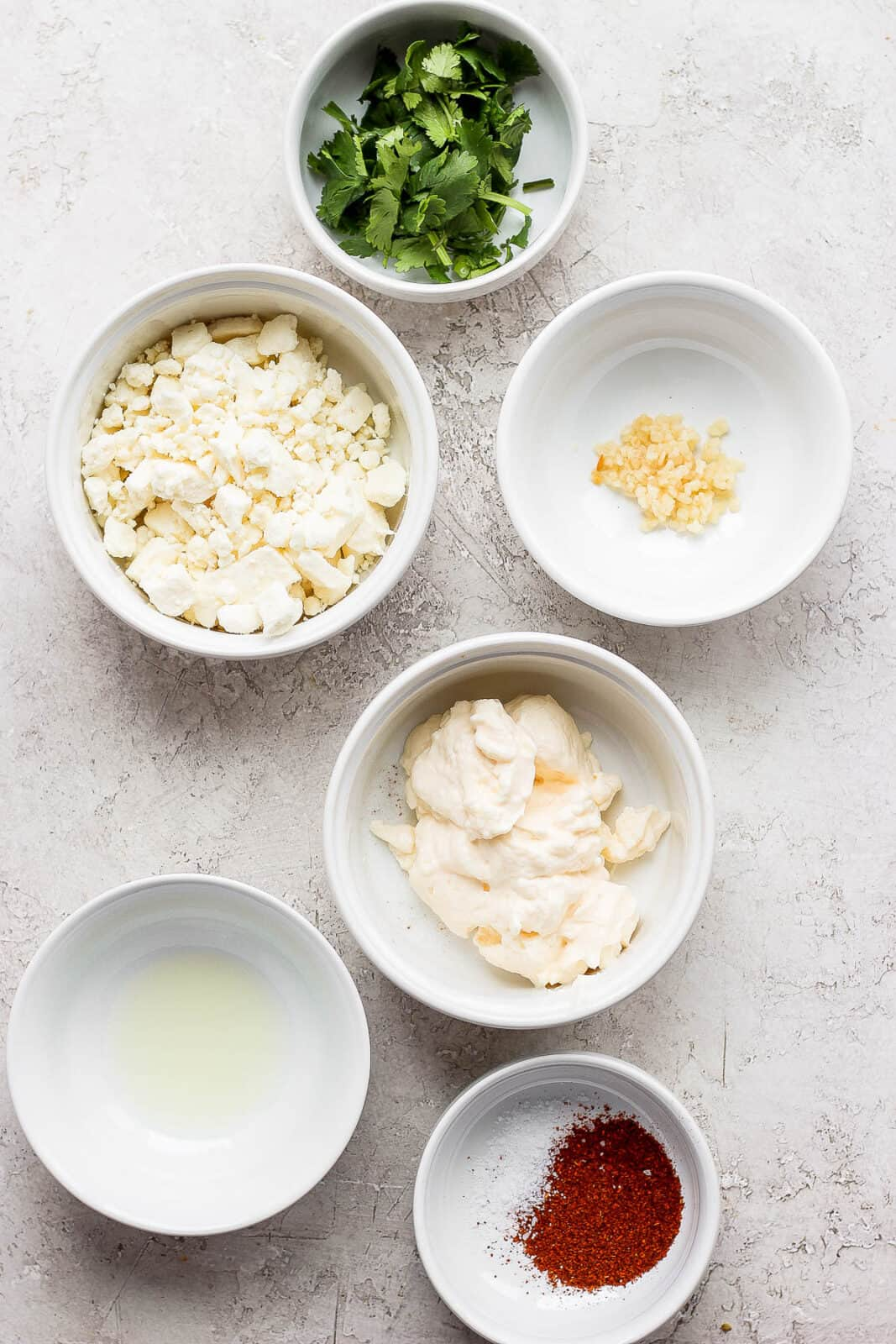 Ingredients for mexican street corn salad in separate bowls.