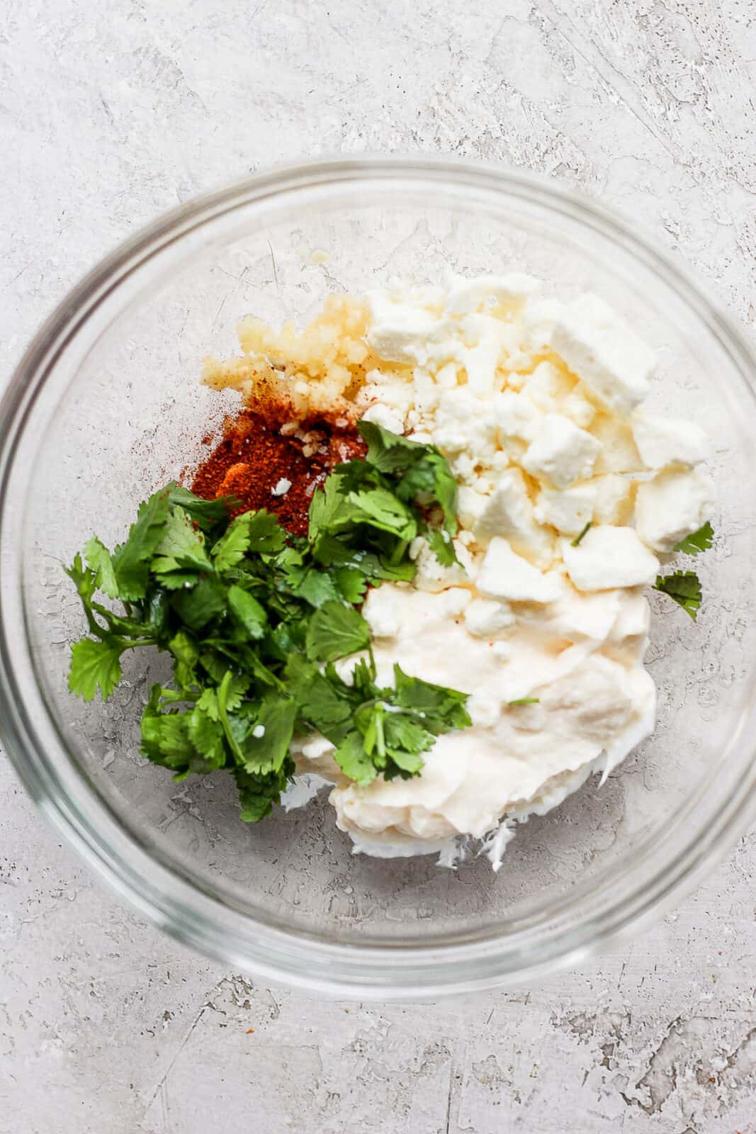 Mayo, feta, cilantro, and spices in a mixing bowl.