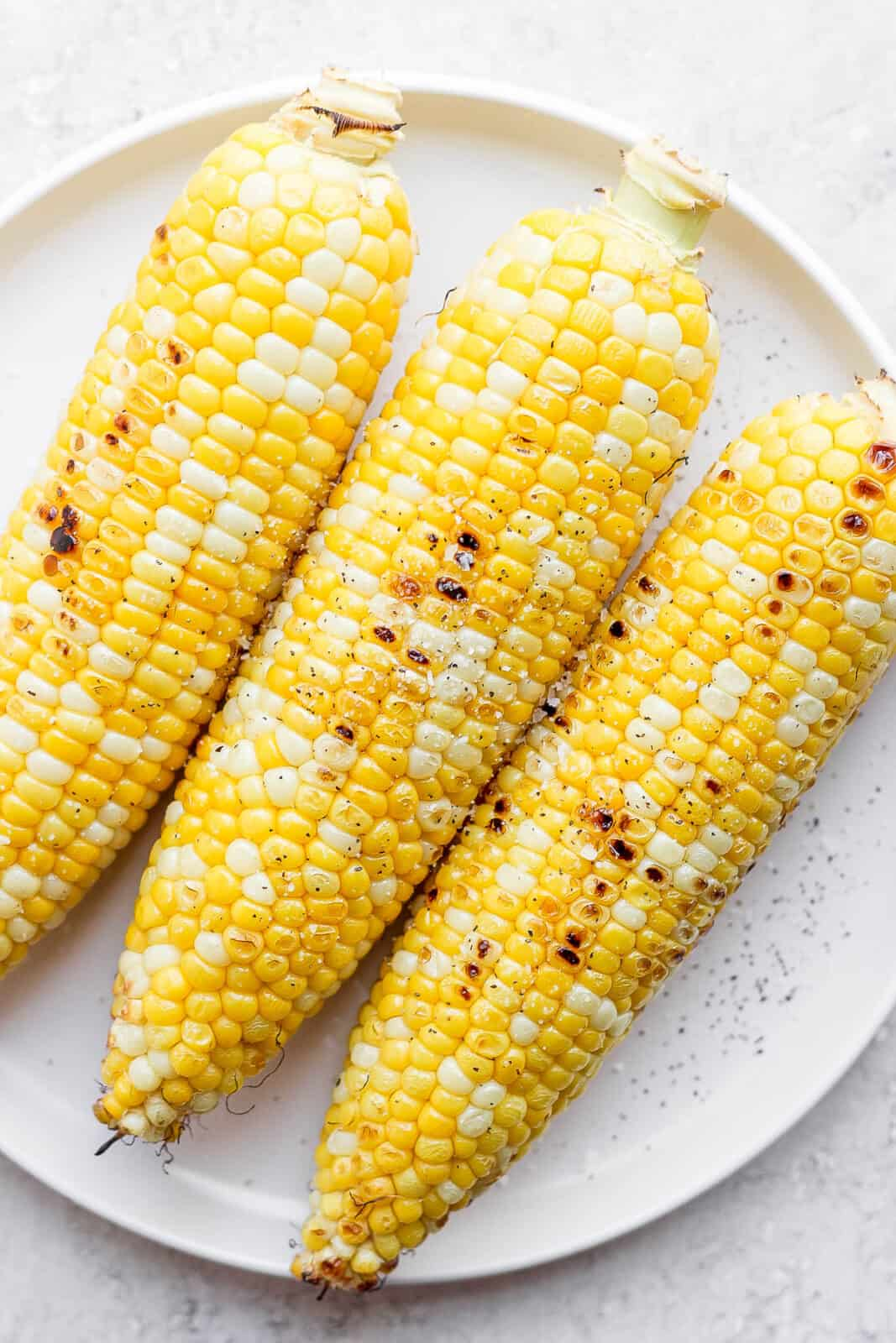 3 ears of grilled corn on the cob on a plate.