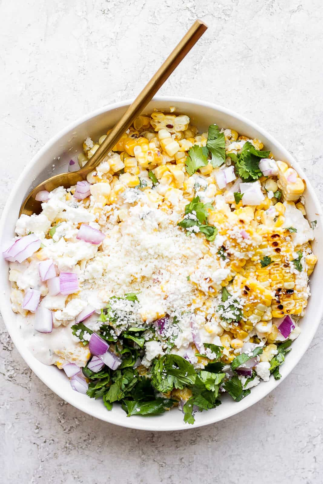 Mexican street corn salad in a bowl with a spoon.