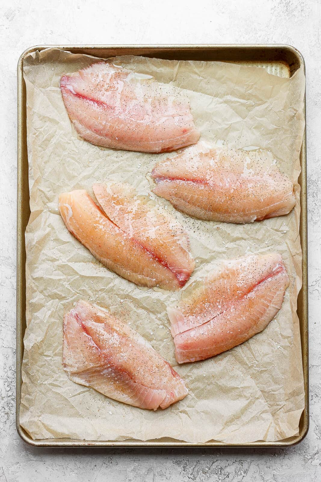 Tilapia fillets on a parchment-lined pan with olive oil, salt, & pepper.