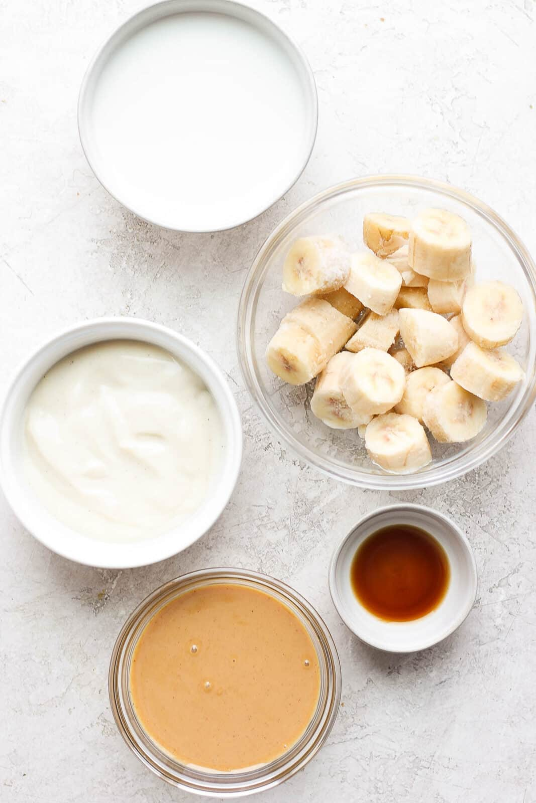 Peanut butter banana smoothie ingredients in small dishes.