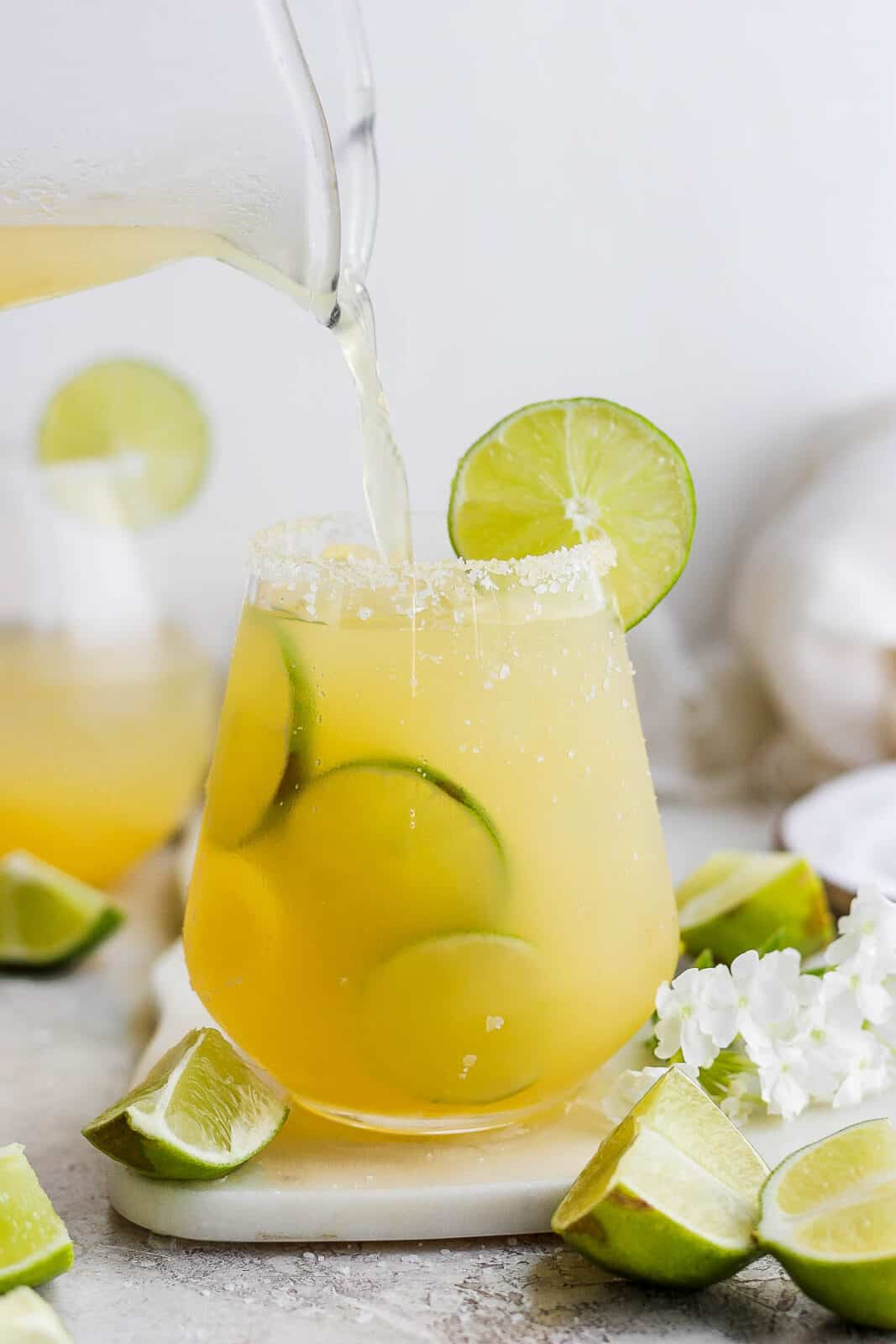 Someone pouring margarita into a salt-rimmed glass.