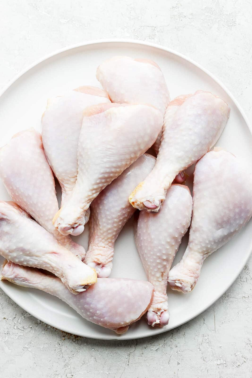 A plate of raw chicken legs.