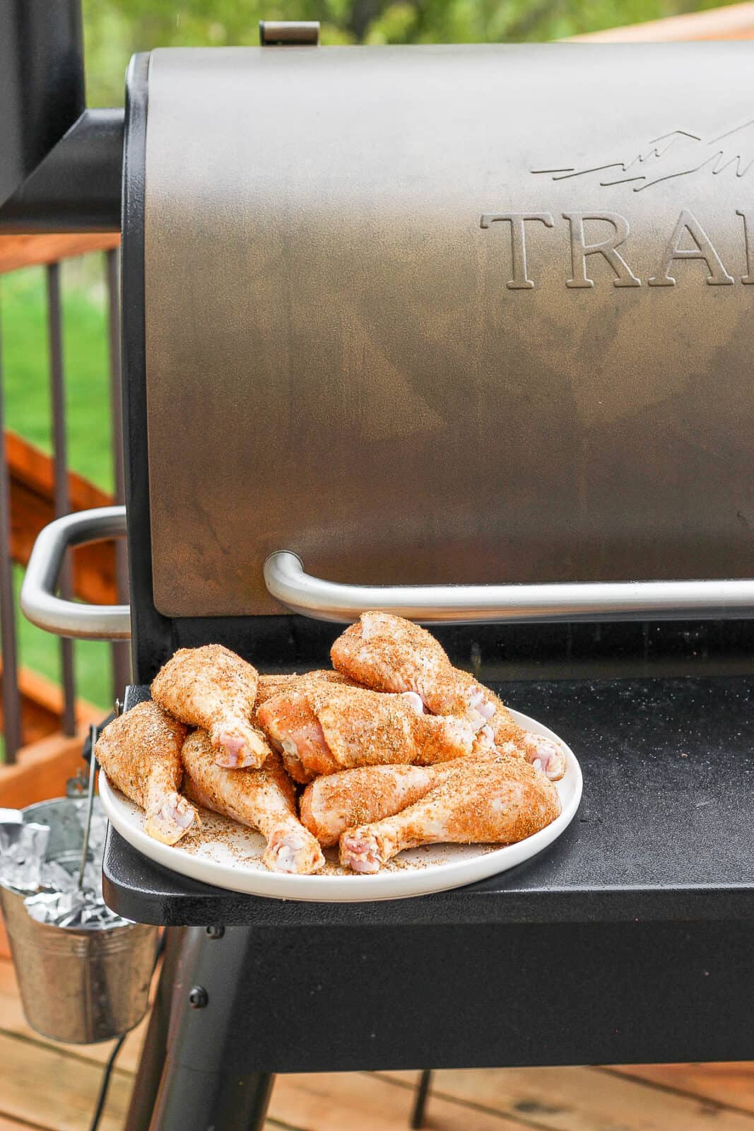 Chicken legs on a plate sitting in front of a smoker.