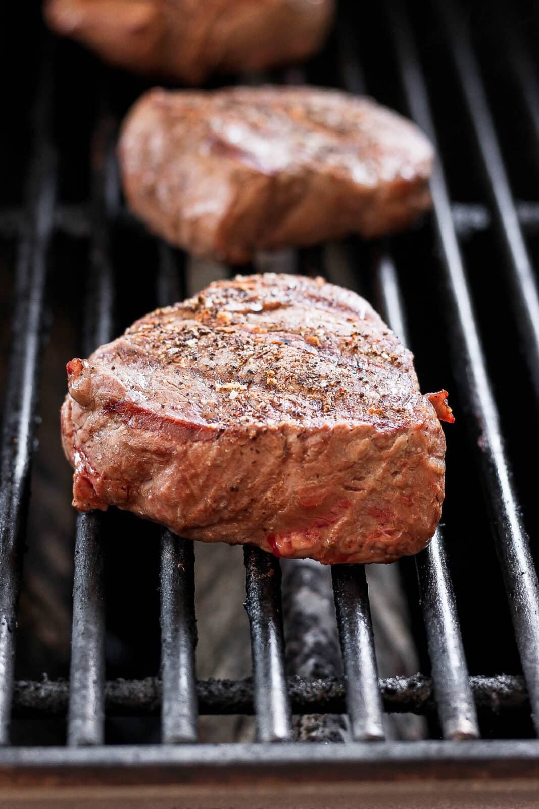 Three steaks on the grill.