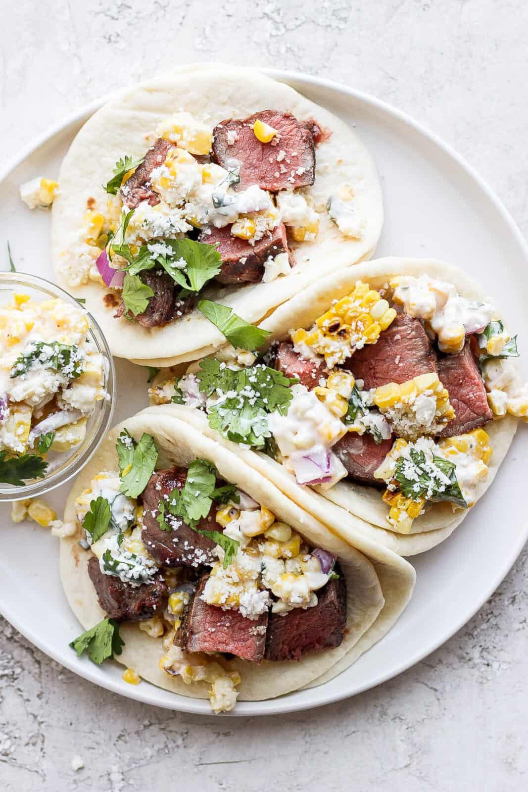 Three steak tacos on a plate.