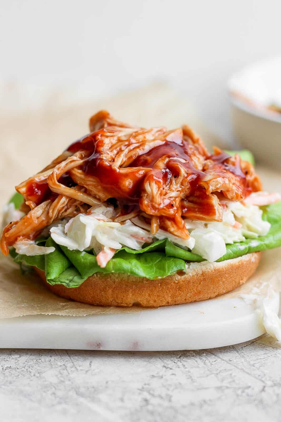 BBQ chicken on a bun with coleslaw and lettuce.