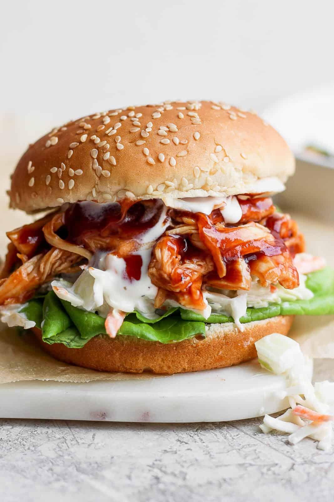 A BBQ chicken sandwich on a plate.