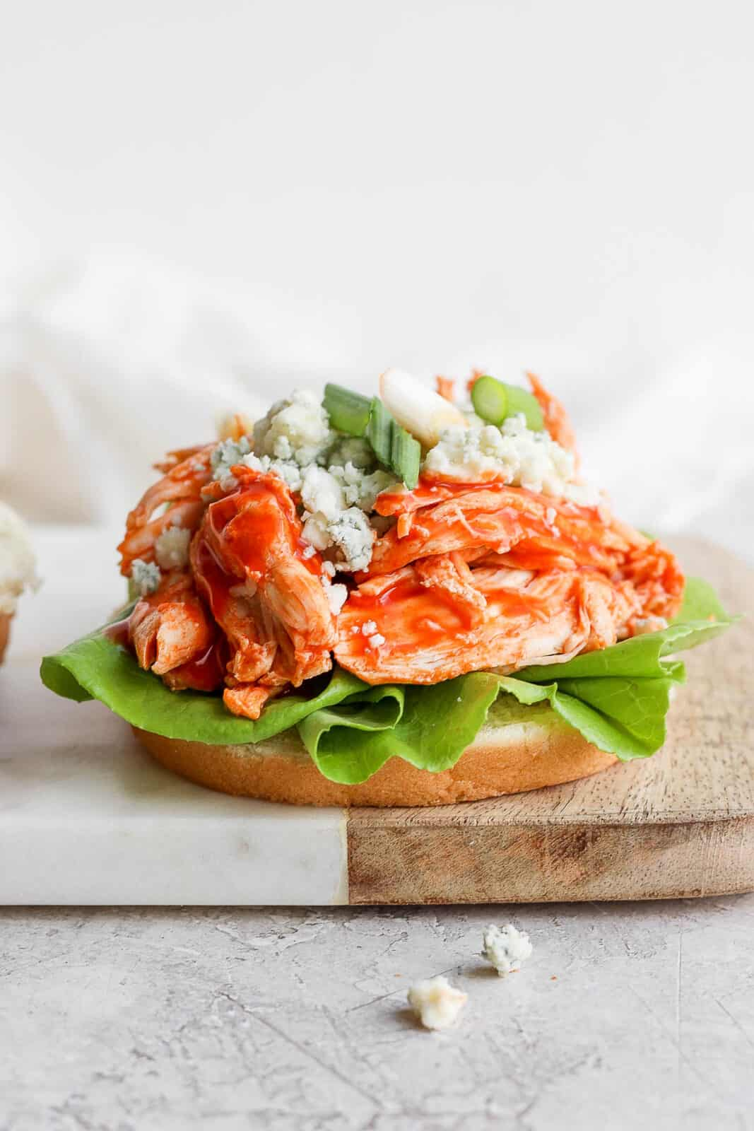 A buffalo chicken sandwich without the top bun on.
