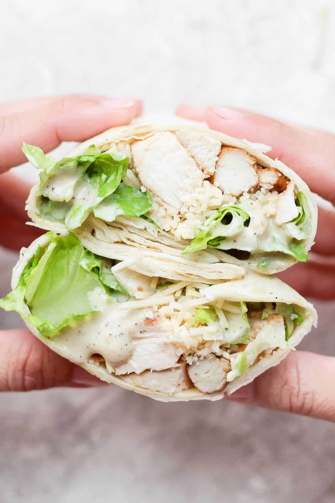 Hand holding a chicken caesar wrap that was cut open in the middle.