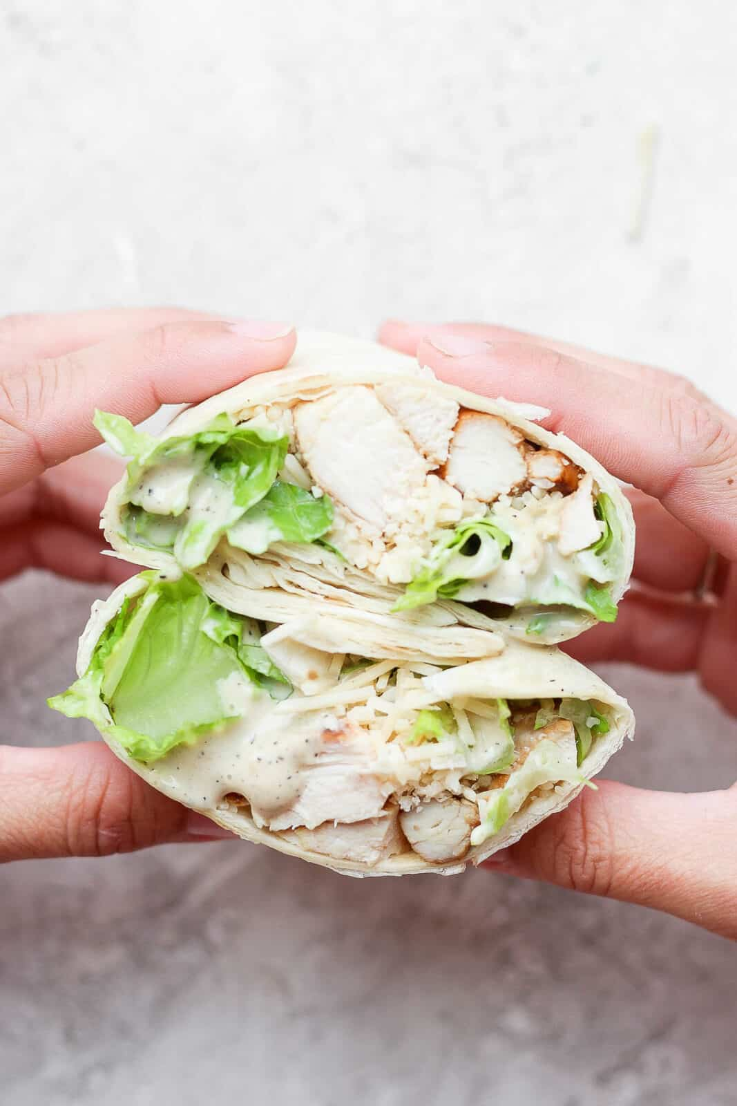 Hands holding a chicken caesar wrap that was cut open in the middle.