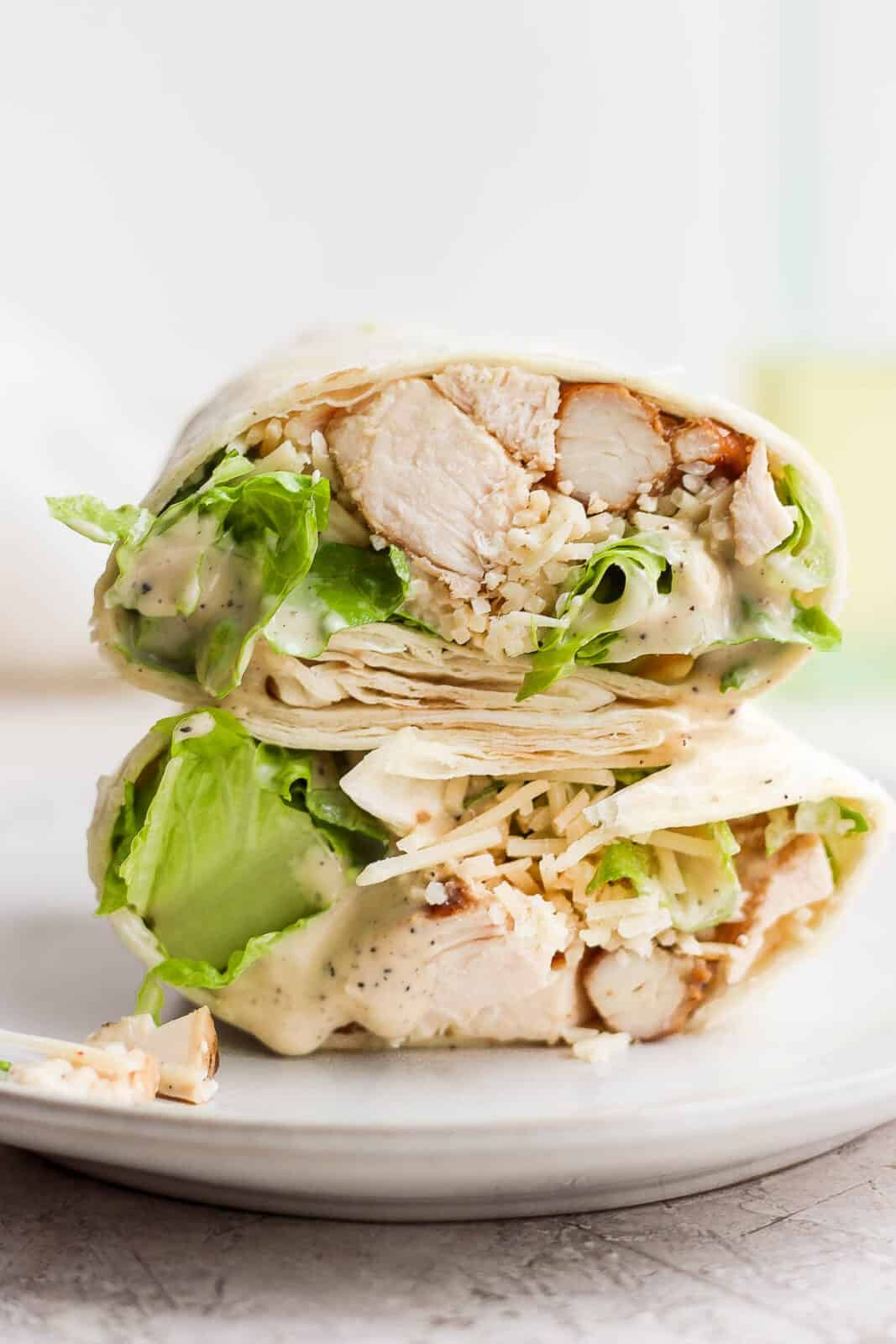 Two halves of a chicken caesar wrap on a plate.