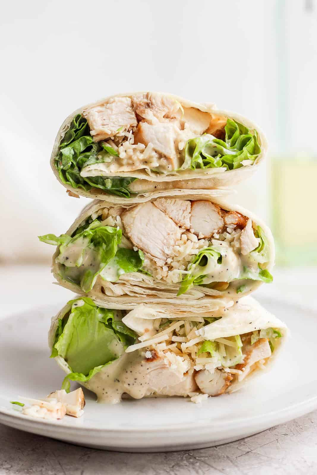 Three halves of chicken caesar wraps on top of each other.