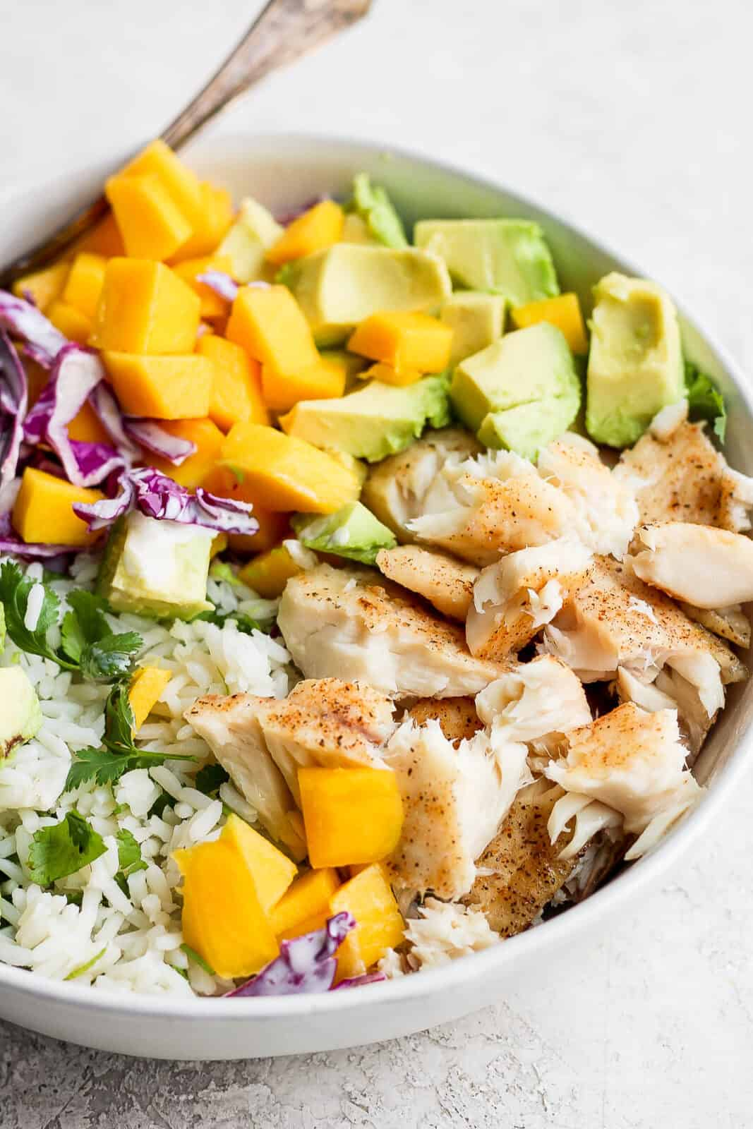Fish taco bowl with rice and a fork.