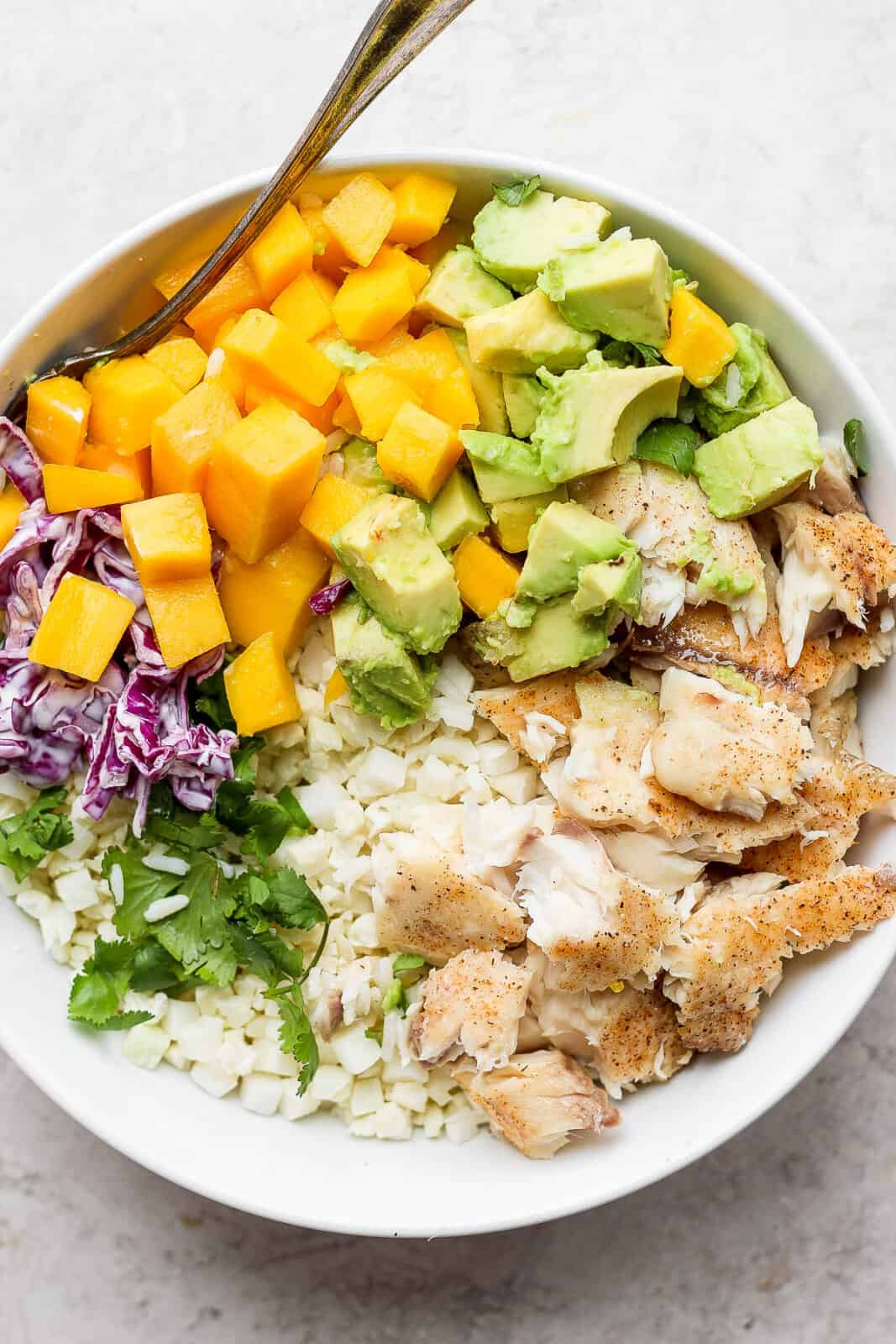 Fish taco bowl with cauliflower rice and a fork.