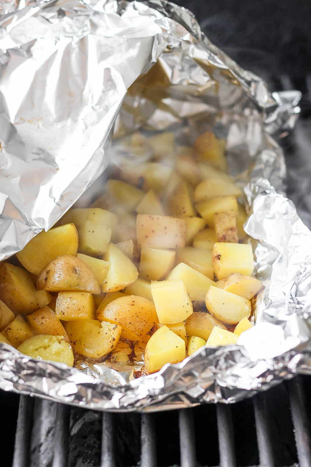Grilled potatoes in a foil boat on the grill with one corner slightly open to see the steam.