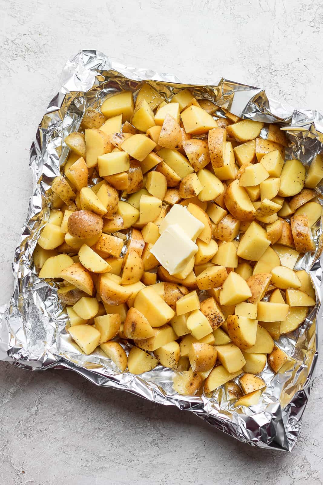 Cut up potatoes in a foil boat with oil, salt, pepper, and butter on top.