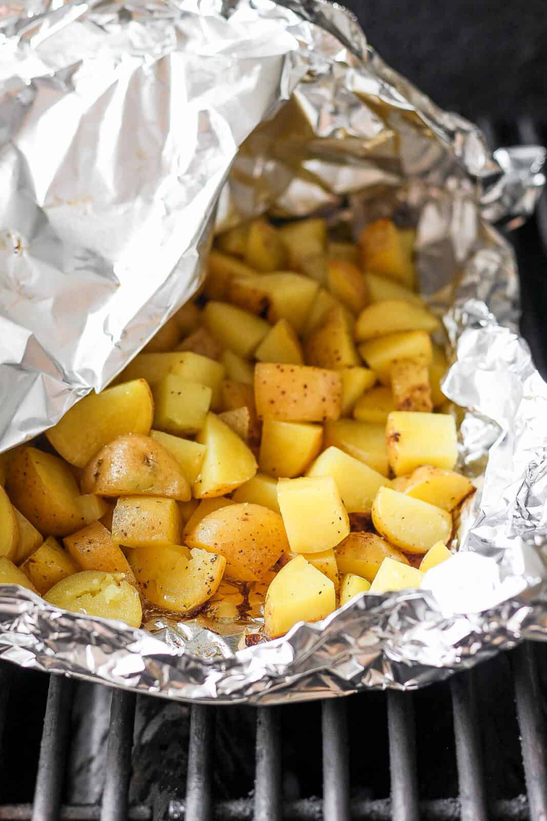 Grilled potatoes in a foil boat on the grill.