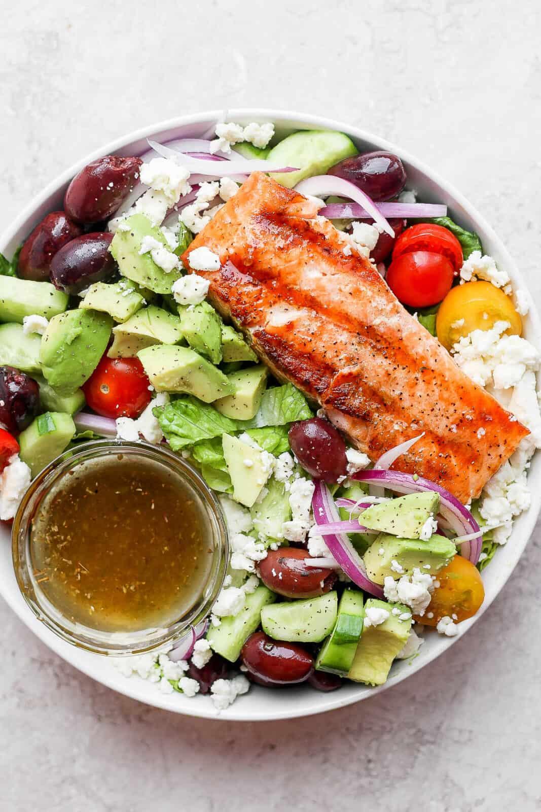 A small dish of greek vinaigrette in a salmon salad.