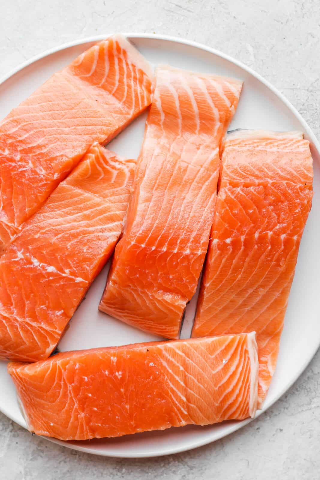 A large plate with raw salmon on it.