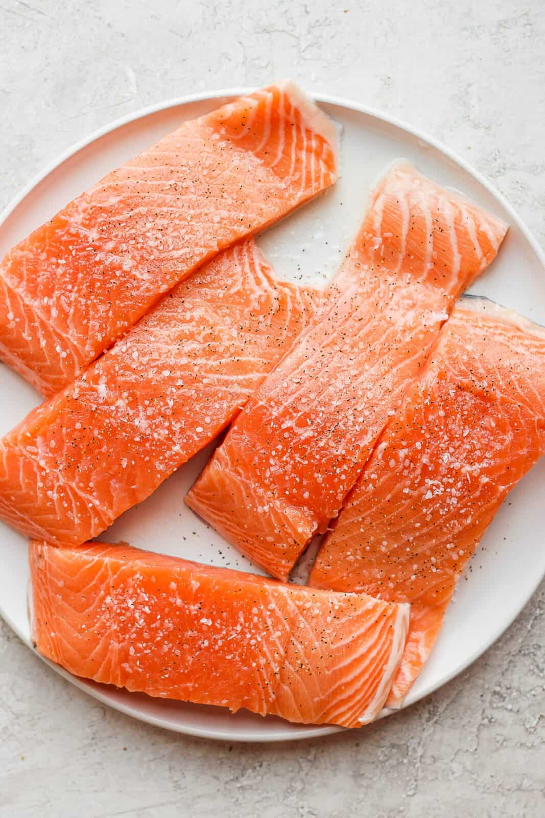 A large plate with salmon on it seasoned with salt and pepper.