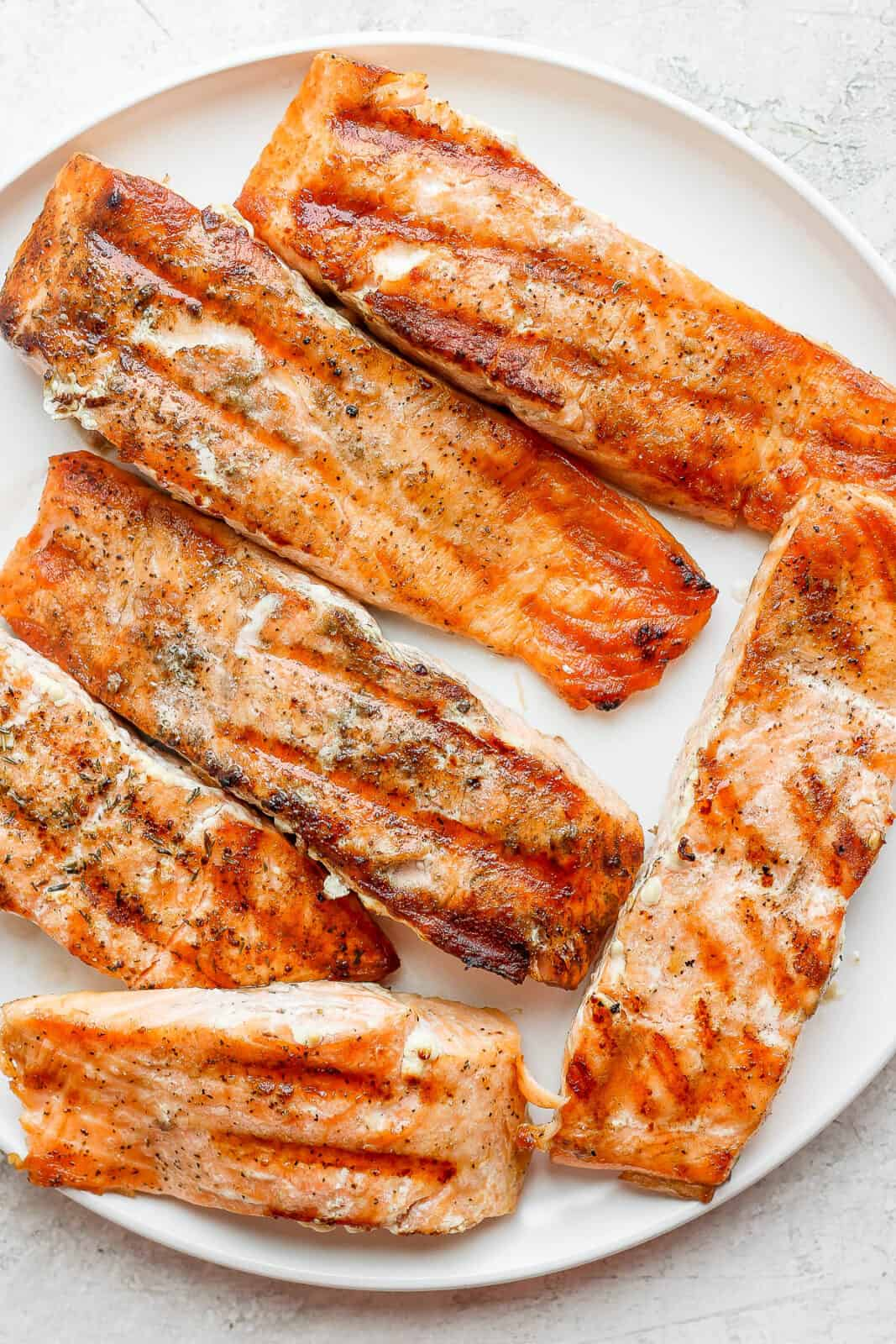 A large plate filled with grilled salmon fillets.