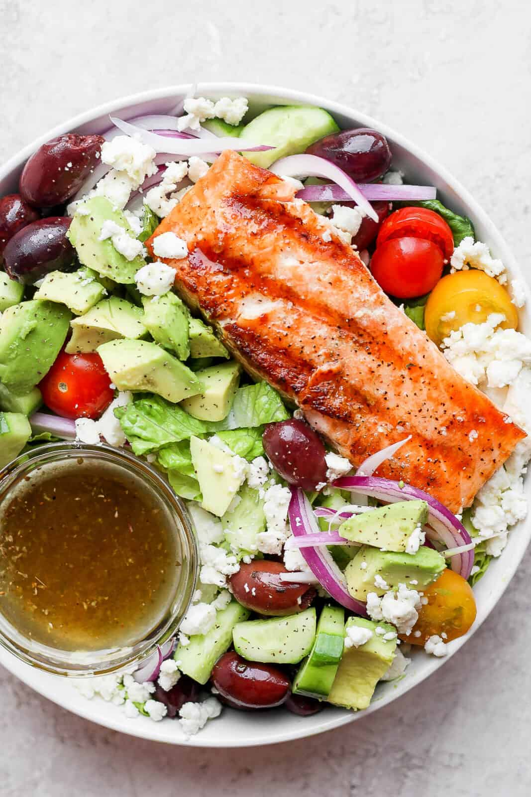 Bowl of grilled salmon salad with avocado, olives and feta cheese.