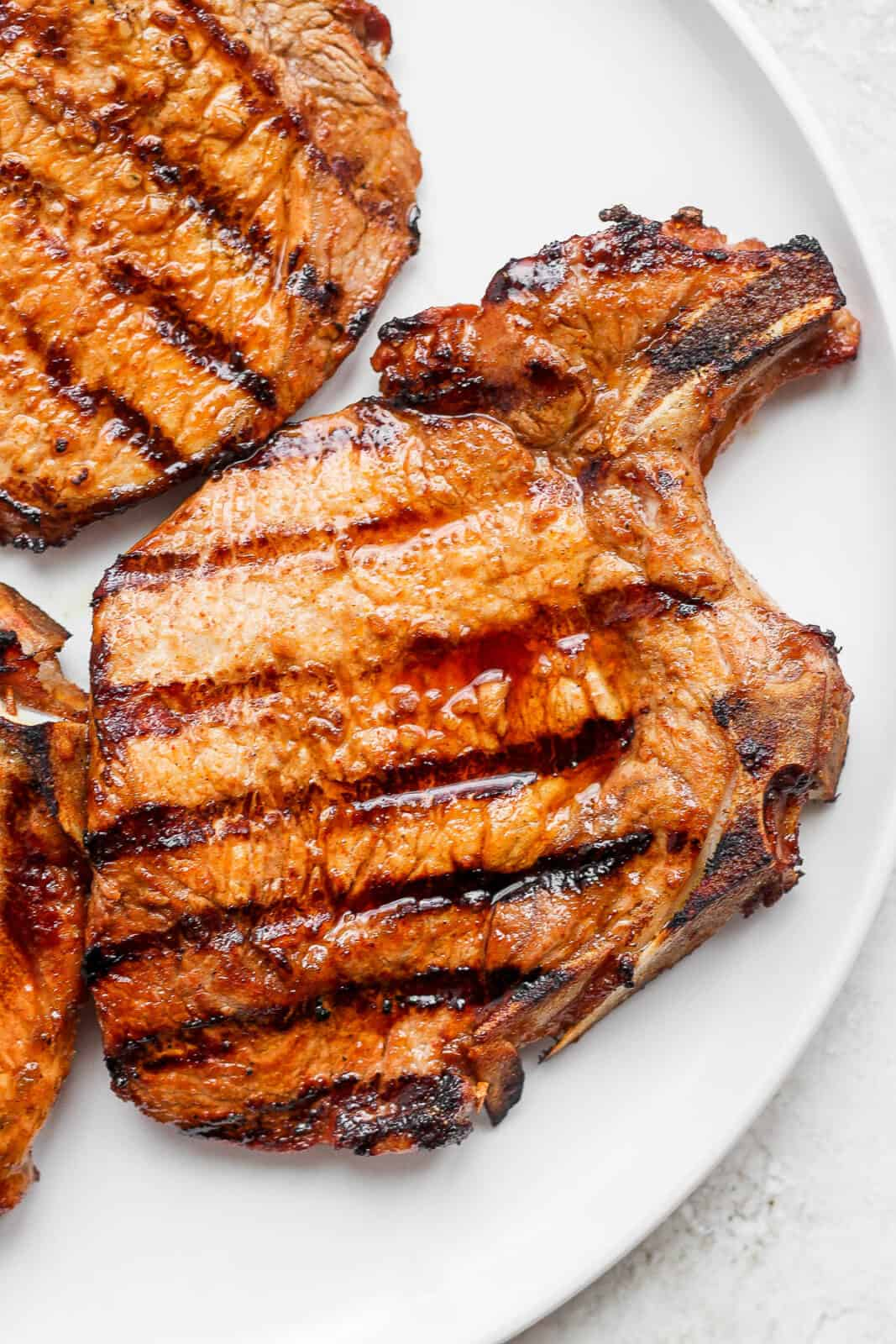 A grilled pork chop on a plate.