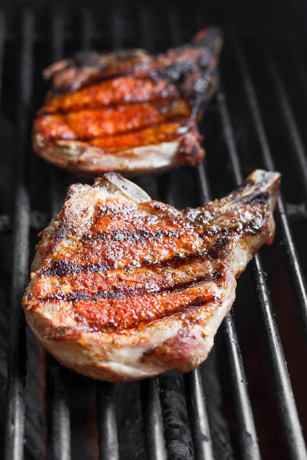 Pork chops cooking on the grill.