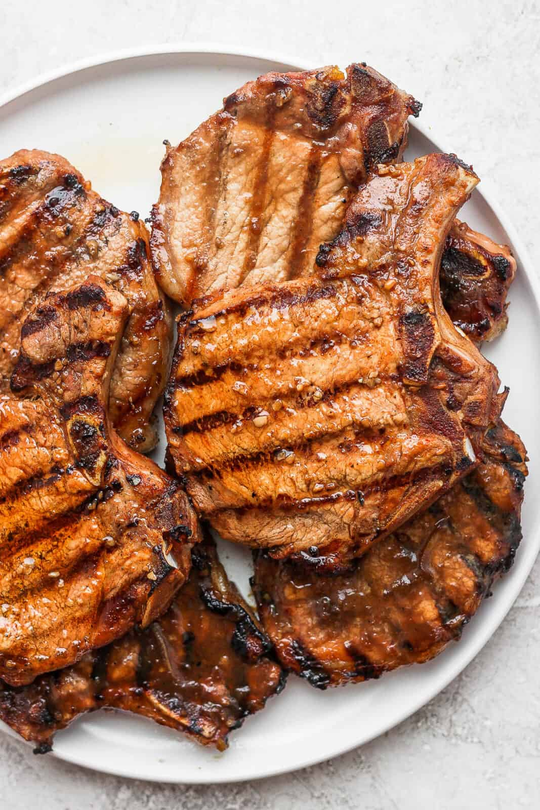Grilled marinated pork chops on a plate.