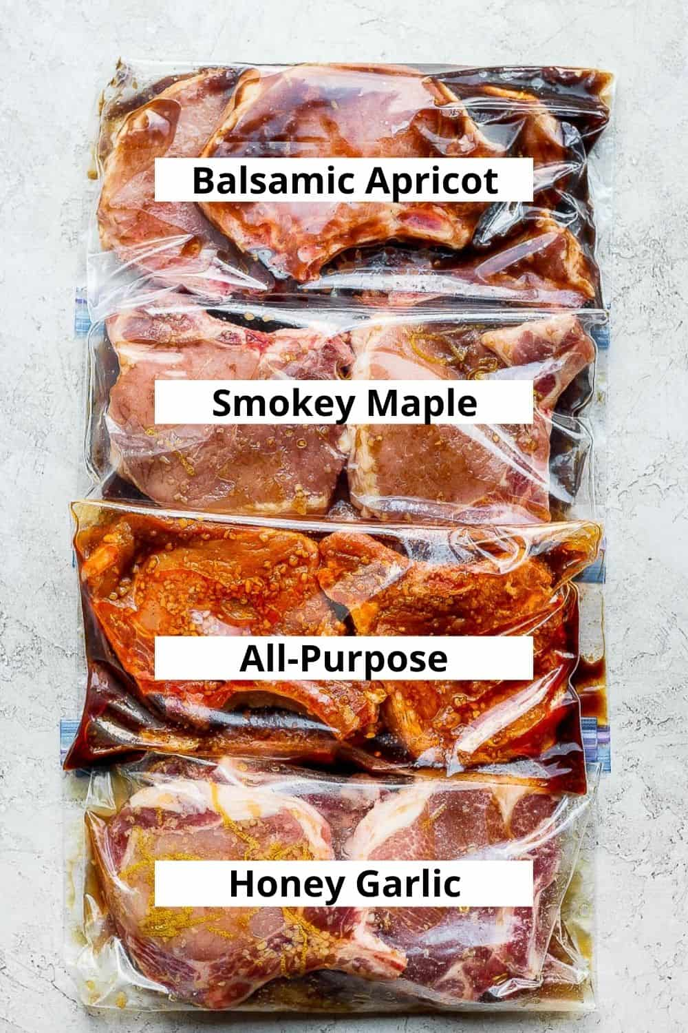 4 different pork chop marinades with uncooked pork chops in plastic bags.