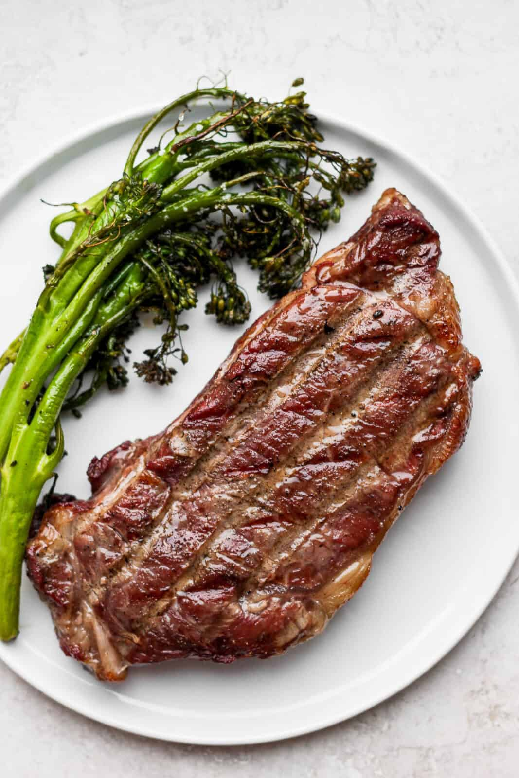 A plate with a reverse seared steak covered in melted butter and parsley with some grilled broccolini next to it.
