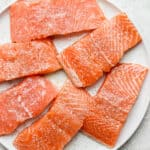 Salmon on a plate with salmon seasoning on top.