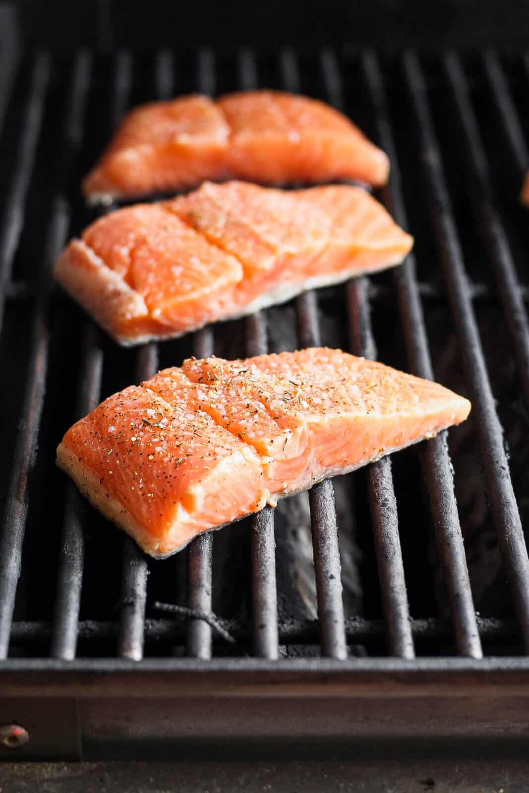 Salmon fillets on the grill with salmon seasoning on top.