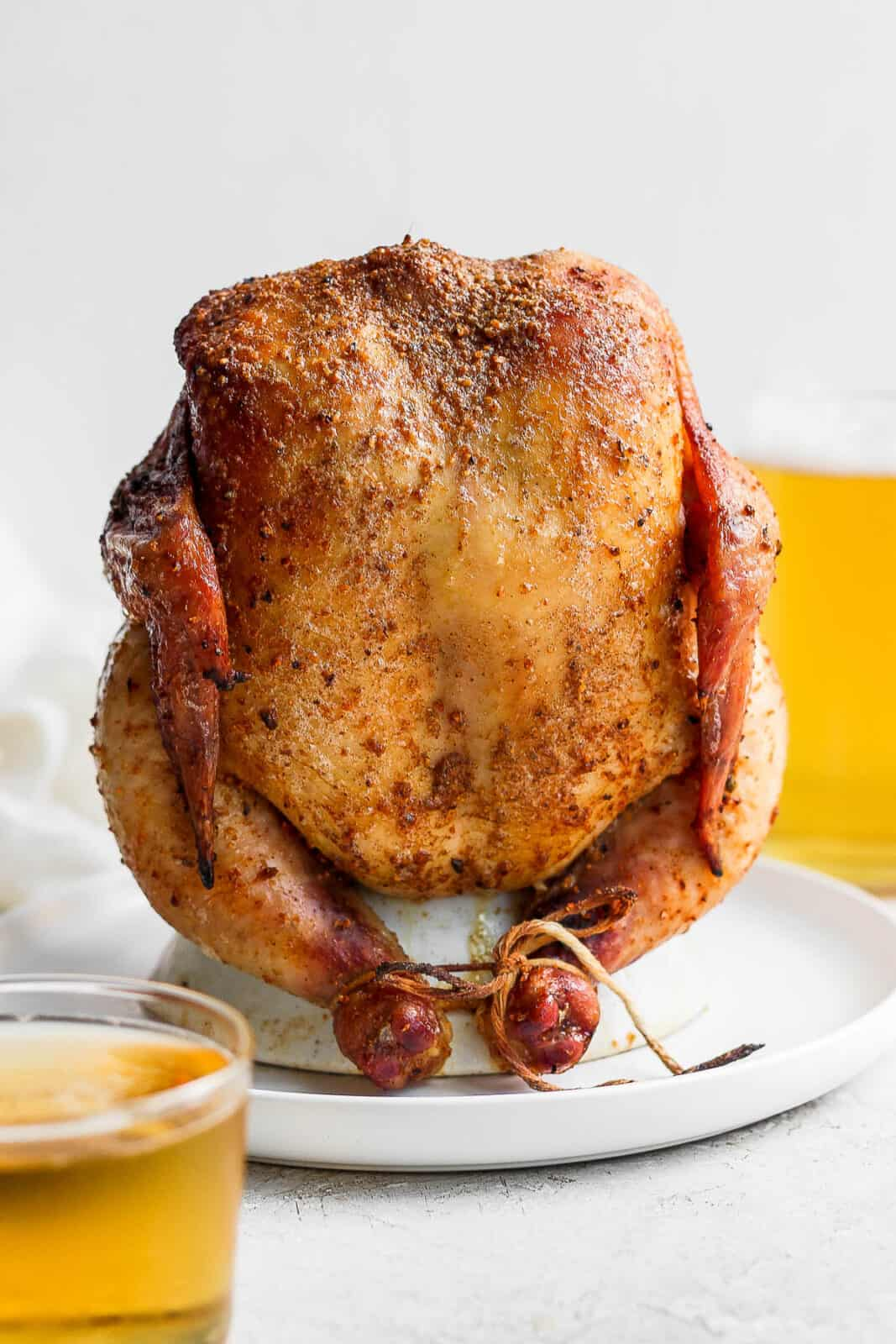 Smoked beer can chicken still on a chicken throne on a plate.