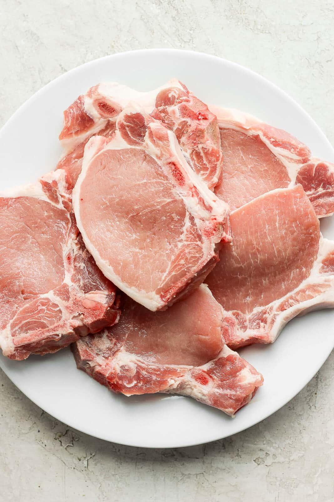 Plate of raw pork chops.