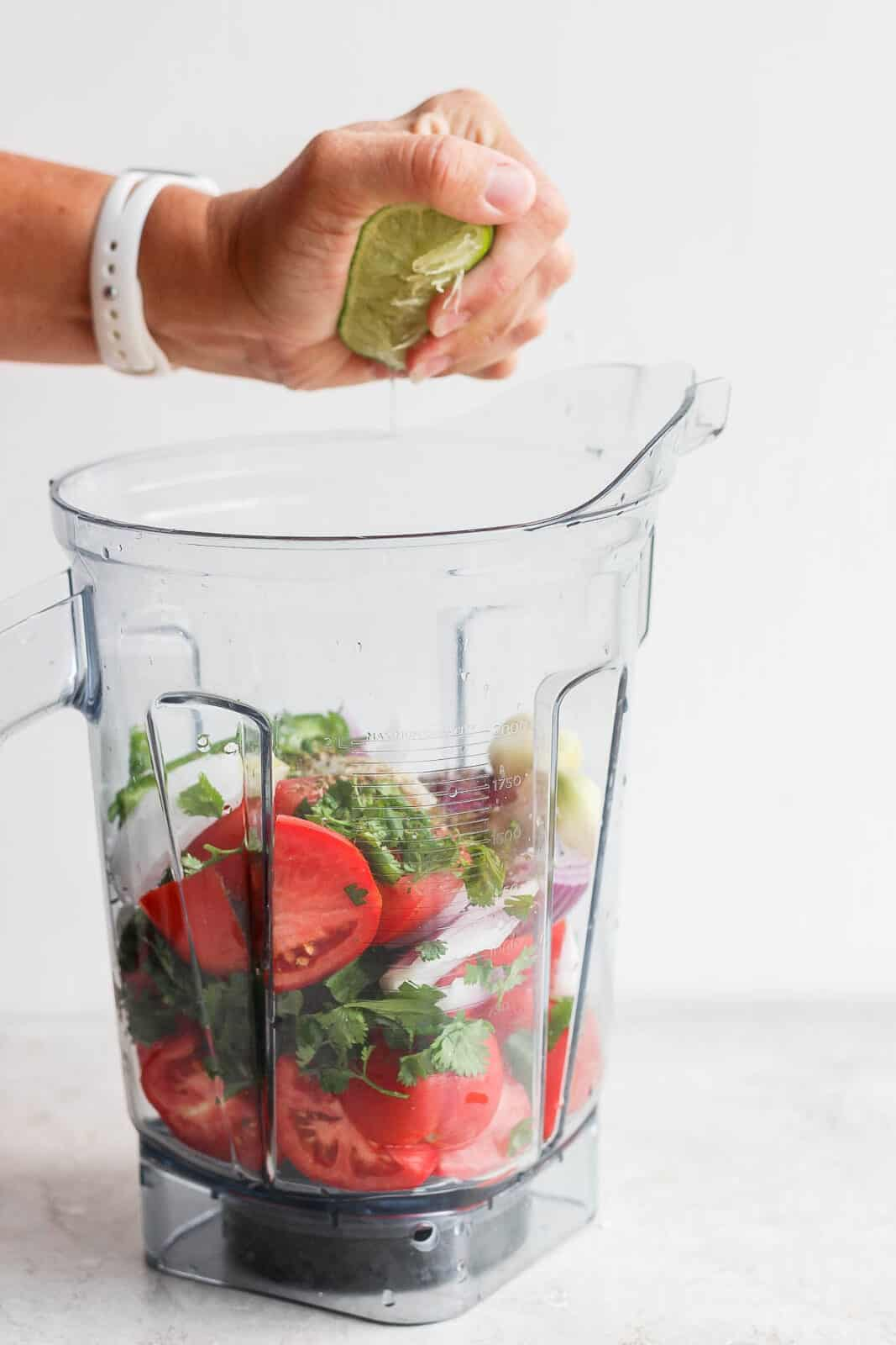 Someone squeezing lime juice into a blender full of salsa ingredients.