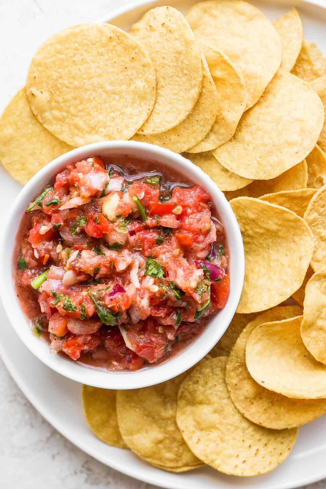 Bowl of blender salsa on a plate of chips.