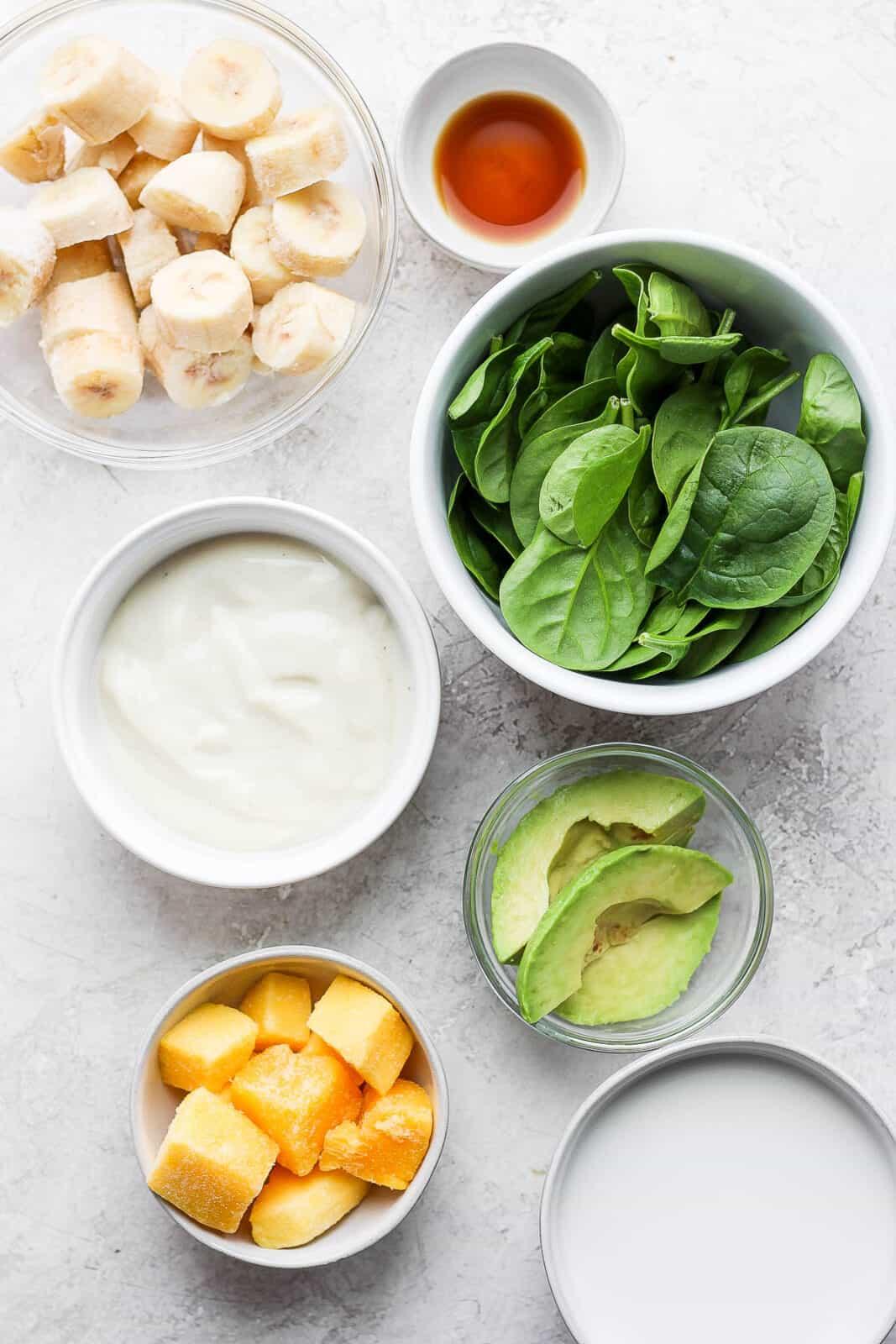 Green smoothie ingredients in separate bowls.