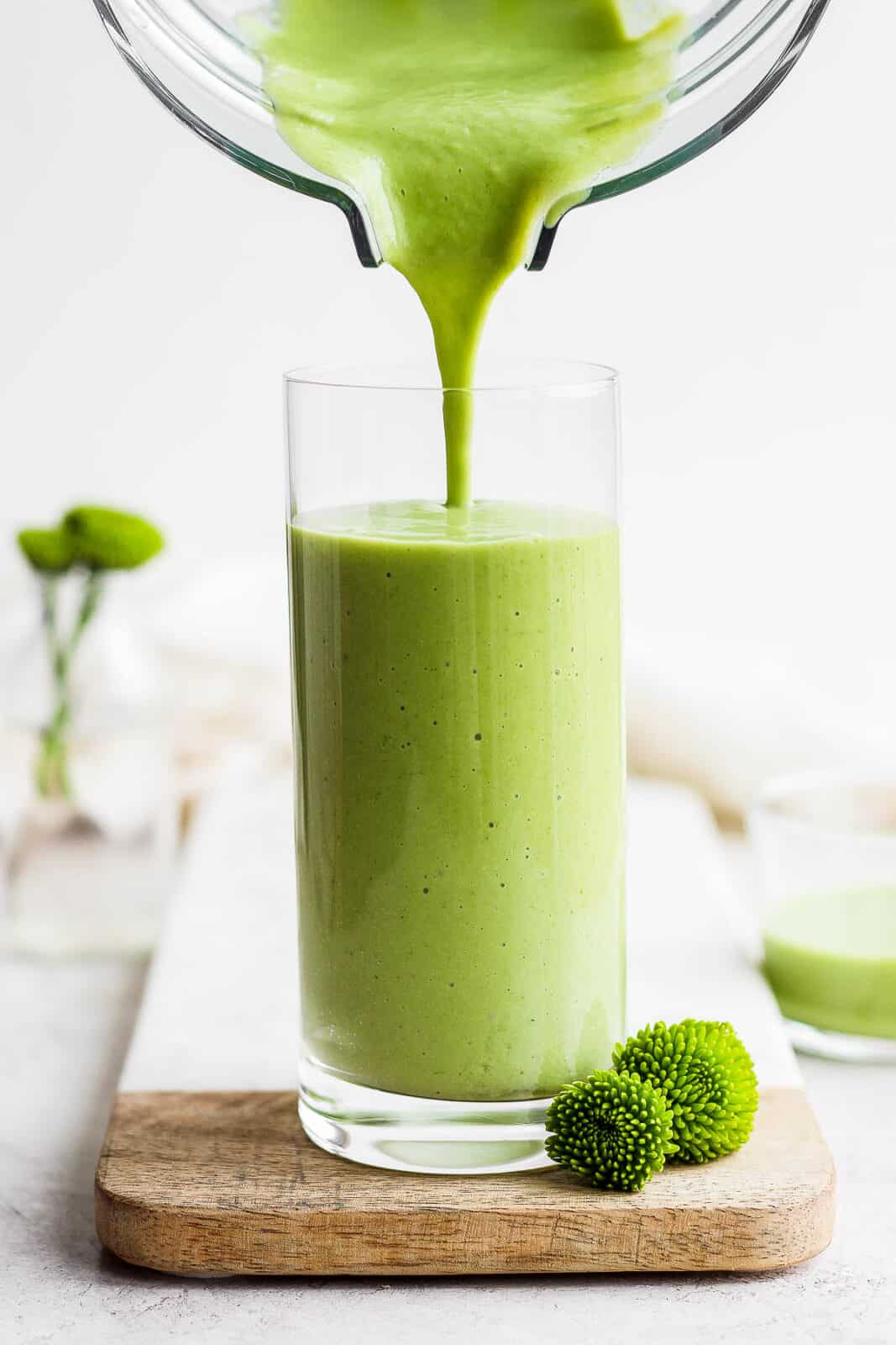 Pouring a green smoothie from a blender into a glass.