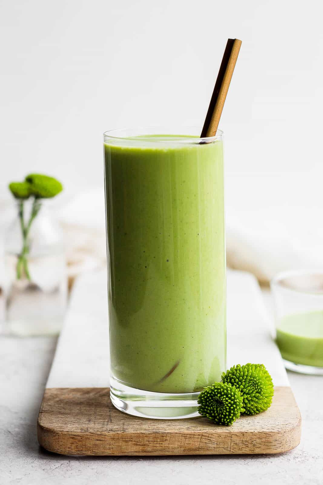 Green smoothie in a glass with a spoon in it.