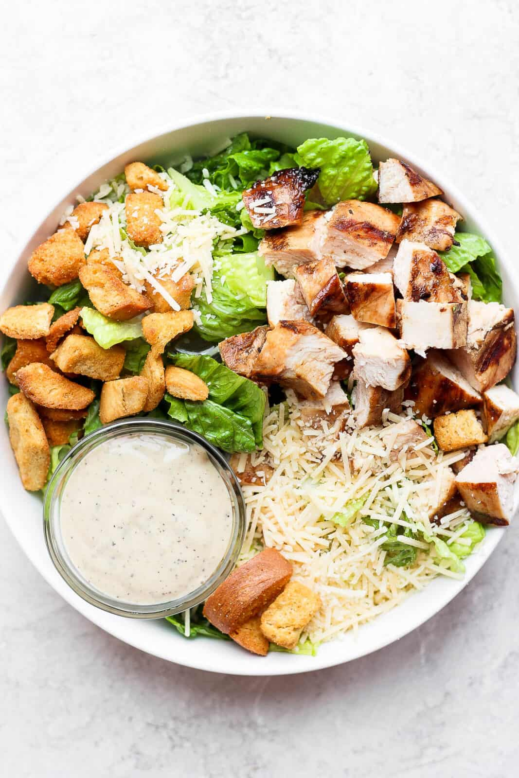 A bowl of grilled chicken caesar salad with a small dish of dressing.