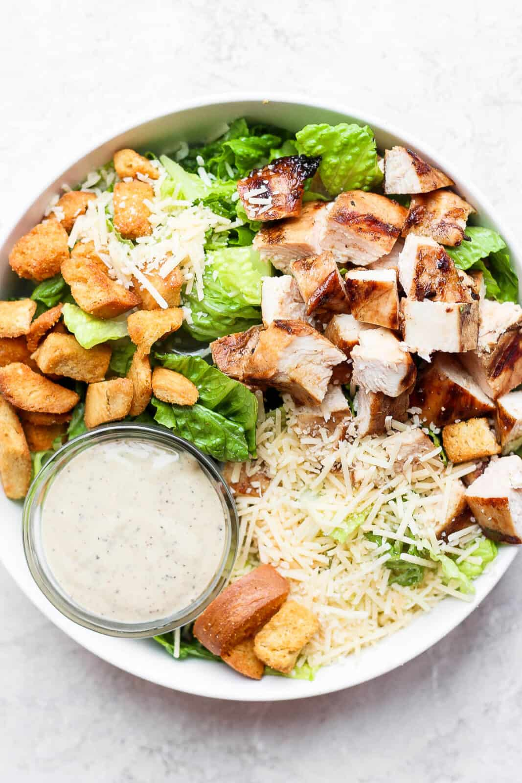 Grilled chicken caesar salad with a small dish of caesar dressing.
